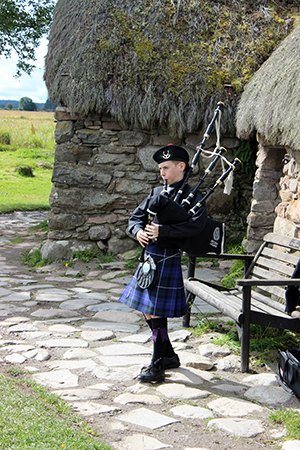 Boy playing bagpipes next to the Culloden Battlefield