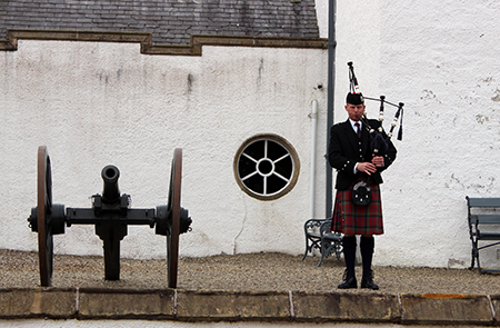 Man in Highland wear playing bagpipes in front of Blair Castle